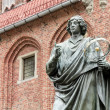 Monument of Copernicus against Town Hall in Torun. Home town of Copernicus. - Stock Photo