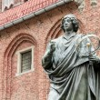 Stock Photo: Monument of Copernicus against Town Hall in Torun. Home town of Copernicus.