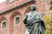 Monument of Copernicus against Town Hall in Torun. Home town of Copernicus. — Stock Photo