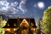 High mountain in Poland. National Park - Tatras. Ecological reserve. Old country house against sky .Shining moon. — Stock Photo