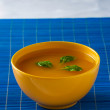Soup in yellow bowl on the blue pad - stock photo — Stock Photo