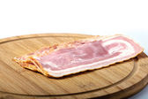 Sliced pork bacon on wood — Stock Photo