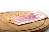 Sliced pork bacon on wood — Stockfoto
