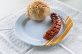 Grilled sausage and bun — Stock Photo