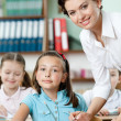 Teacher helps pupils to perform task — Stock Photo #12418878