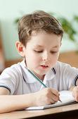 écolier fait quelques notes sur la feuille de papier, gros plan — Photo