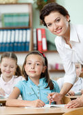 Teacher helps pupils to perform the task — Stock Photo