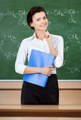 Smiley teacher at the blackboard holds writing pad — Stock Photo