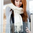 Woman in scarf looking at the bakery window — Stock Photo #12563755