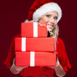 Attractive woman in Christmas cap hands a set of presents — Stock Photo