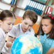 Pupils are seeking for something at the school globe — Stock Photo