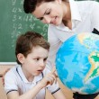 Stock Photo: Little schoolboy looks at the terrestrial globe