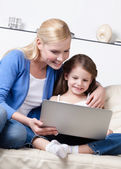 Little child surfs on the internet with her mum — Stock Photo