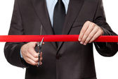 A businessman cutting a satin ribbon — Stock Photo
