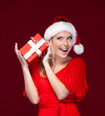 Young woman in Christmas cap hands a gift wrapped with red paper — Stock Photo