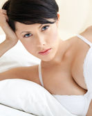 Woman in bra is lying in the bed with white bedclothes — Stock Photo