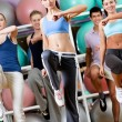 Sexy female coach does exercises with her group — Stock Photo