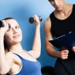 Personal coach controls sports actions of pretty woman — Stock Photo #12748642
