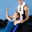 Athletic trainer helps woman to exercise with weights — Stock Photo