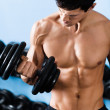 Stock Photo: Sexy muscular muses his dumbbell