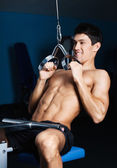 Athletic man works out on gym equipment — Stock Photo
