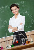 Smiley chemistry teacher with crossed arms — Stock Photo