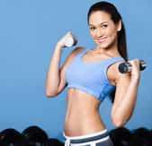 Woman exercises with dumbbells — Stock Photo