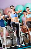 Entrenador femenino sexy hace ejercicios con su grupo — Foto de Stock