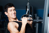 Athletic man works out on fitness gym equipment — Stock Photo
