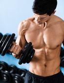 Sexy muscular man uses his dumbbell — Stockfoto