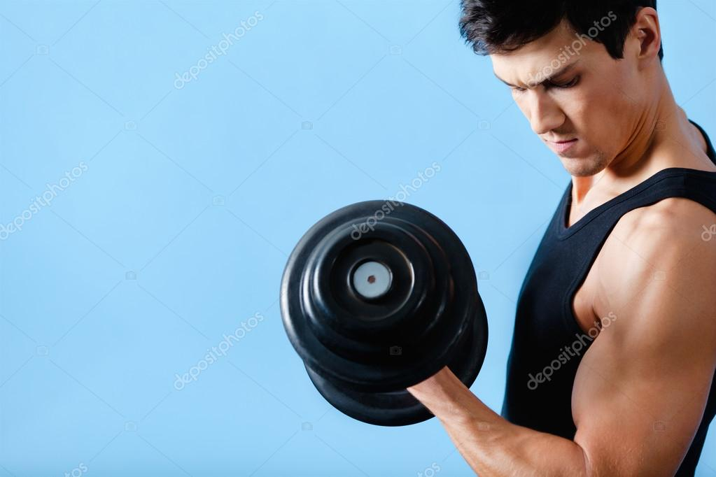 Handsome muscular man uses his dumbbell to exercise flexing bicep muscle — Stock Photo #12748831