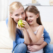 Royalty-Free Stock Photo: Smiley mother with her eating apple daughter