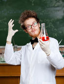 Mad professor admires his experimental red liquid — Stock Photo