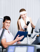 Athletic woman training on gym equipment in gym with coach — Stock Photo