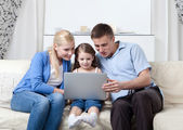 Happy family sit on the couch with laptop — Stock Photo