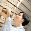Pretty woman researches something in card catalog — Stock Photo #12865525