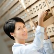 Pretty girl looks for something in card catalog — Stock Photo #12865912