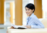 Pretty businesswoman rests at the sofa with book — Stock Photo