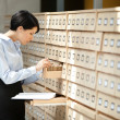 Woman seeks something in card catalog — Stock Photo