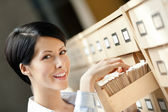 Young female searches something in card catalog — Stock Photo