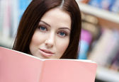 Female student reads the book at the library — Stock Photo