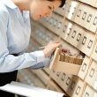 Pretty woman searches something in card catalog — Stock Photo