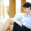 Pretty woman rests at the sofa with book — Stock Photo