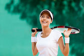 Successful sportswoman with racket at the tennis court — ストック写真