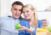 Pretty woman offers an apple to her husband — Stock Photo