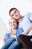 Happy couple sits on the white leather sofa — Stock Photo