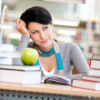 Dreamy female student studies at the reading hall — Stock Photo