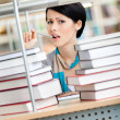 Student surrounded with books in panic — Stock Photo