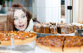 Girl in scarf looking at the bakery showcase — Stock Photo