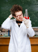 Mad professor holds Erlenmeyer flask — Stock Photo